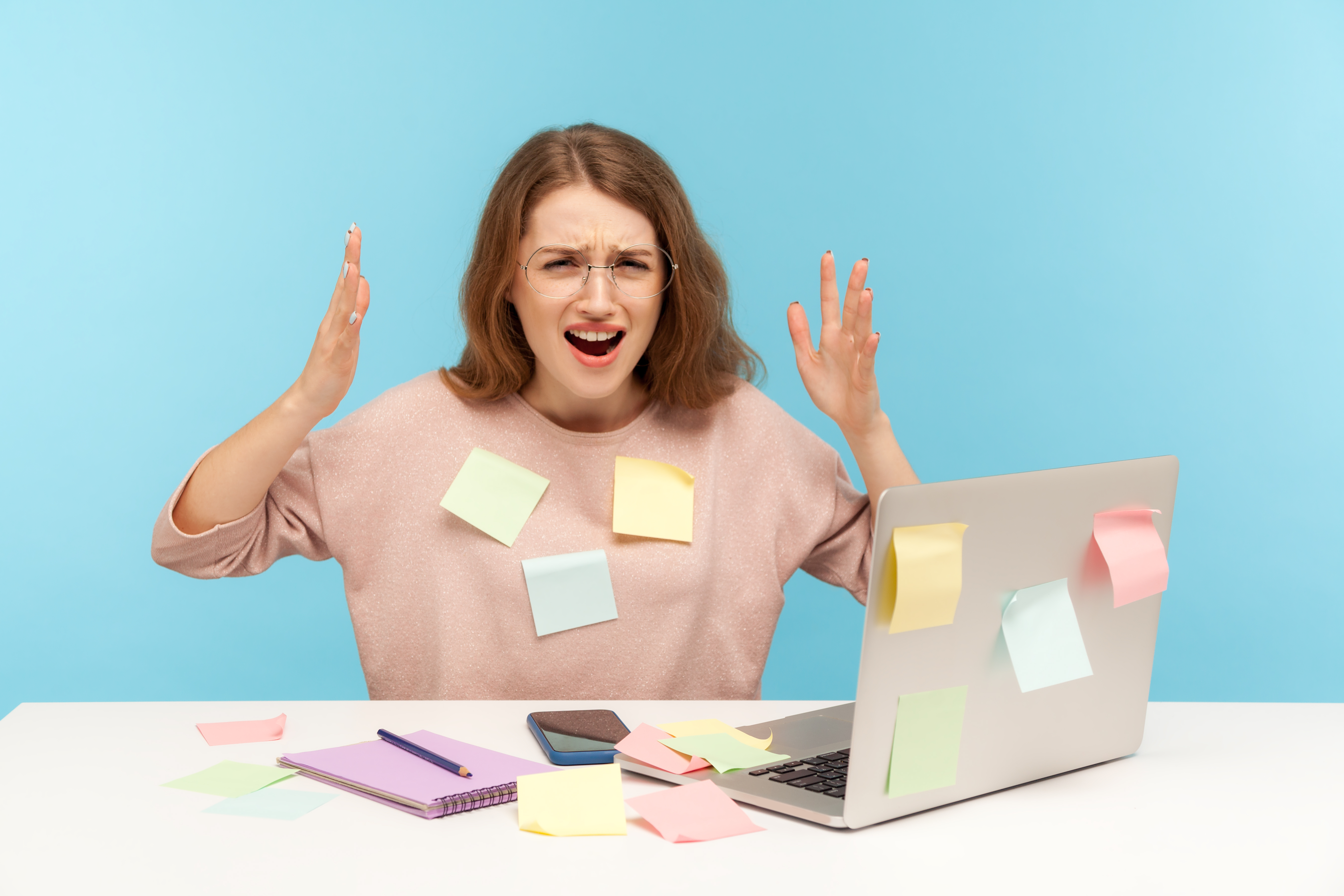 Overwhelmed women with sticky notes all over herself and work station.