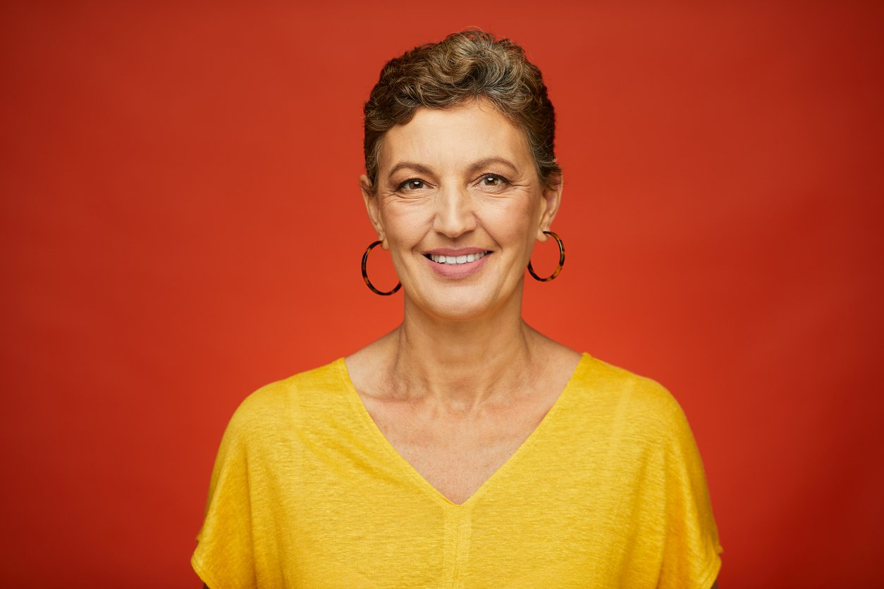 Smiling woman with earrings and yellow shirt with a red background