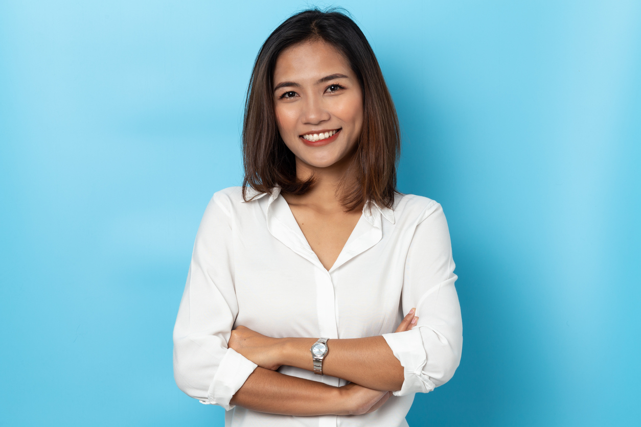 Smiling woman in a white shirt with a blue background