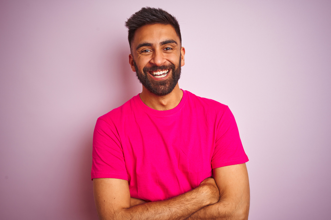 Smiling man with a pink shirt and a pink background