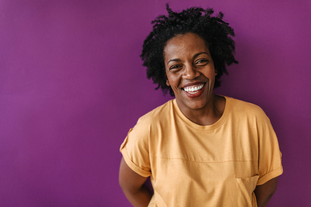 Smiling woman in yellow shirt with purple background