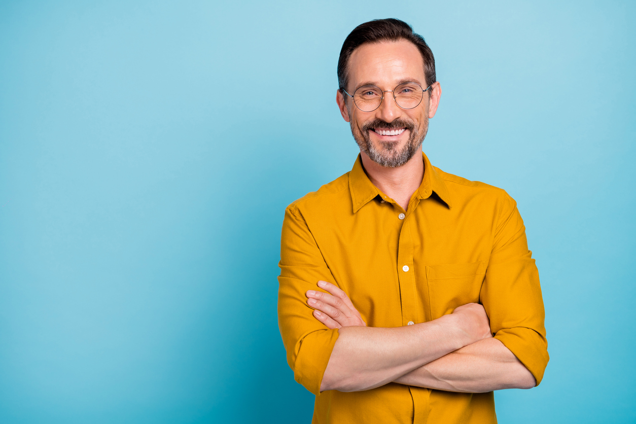 Smiling man with glasses with an orange shirt and a blue background